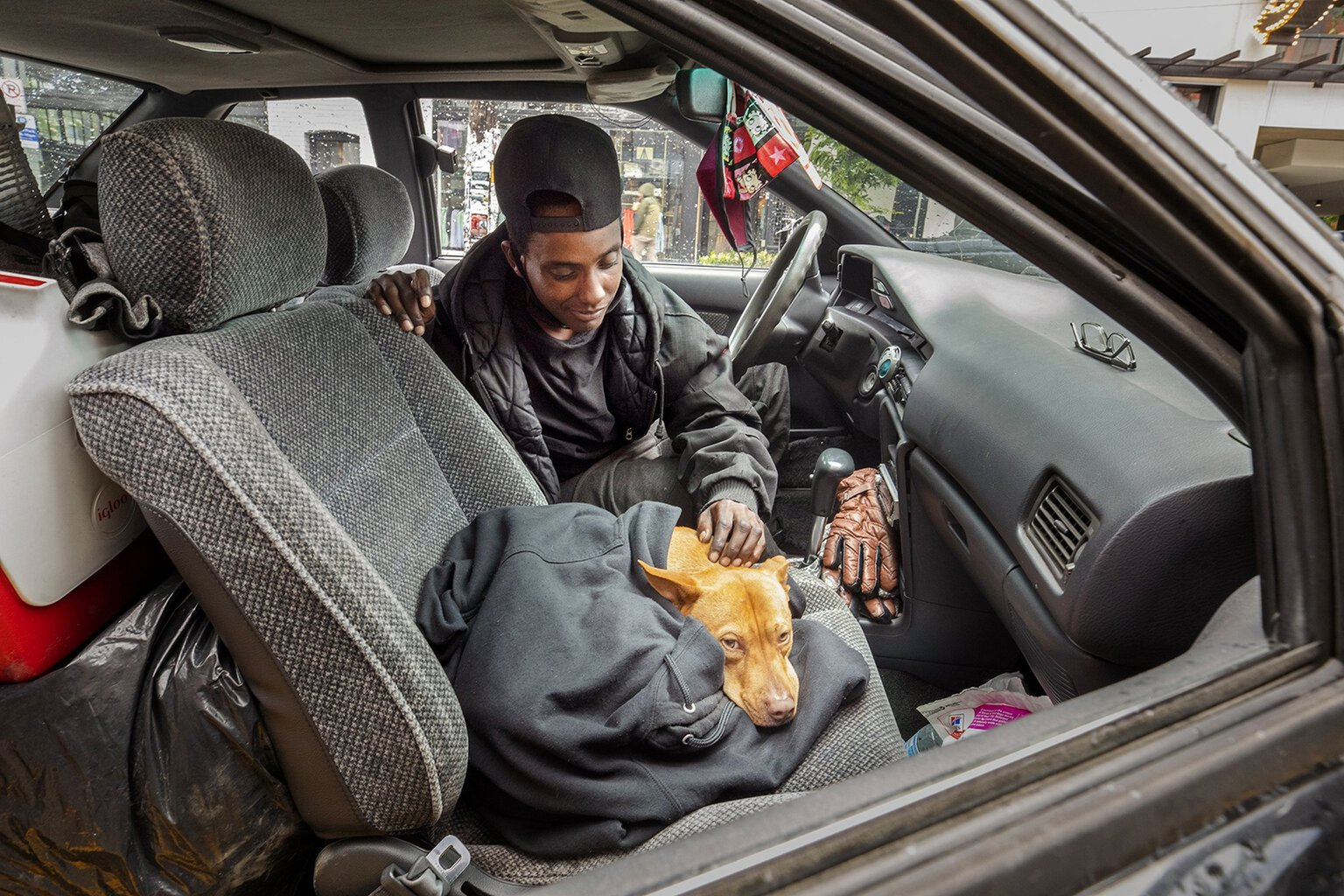 A woman and her dog live in her car together.